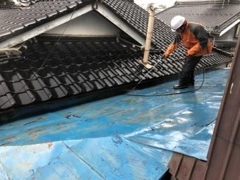 青く塗られた古いトタン屋根を洗っている様子
