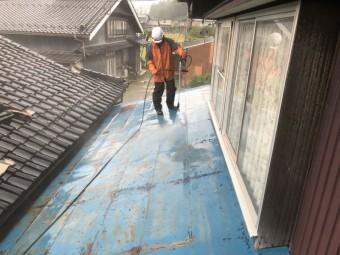 青く塗られた古いトタン屋根を洗っているいる様子