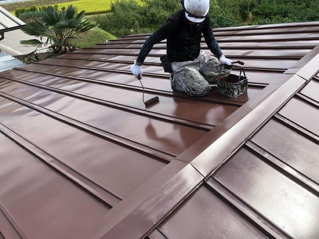 屋根の上塗りをしている様子