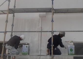 足場を組み白いペンキを塗っている作業員